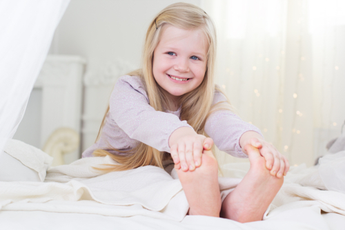 Happy blonde child girl is sitting barefoot in the bed