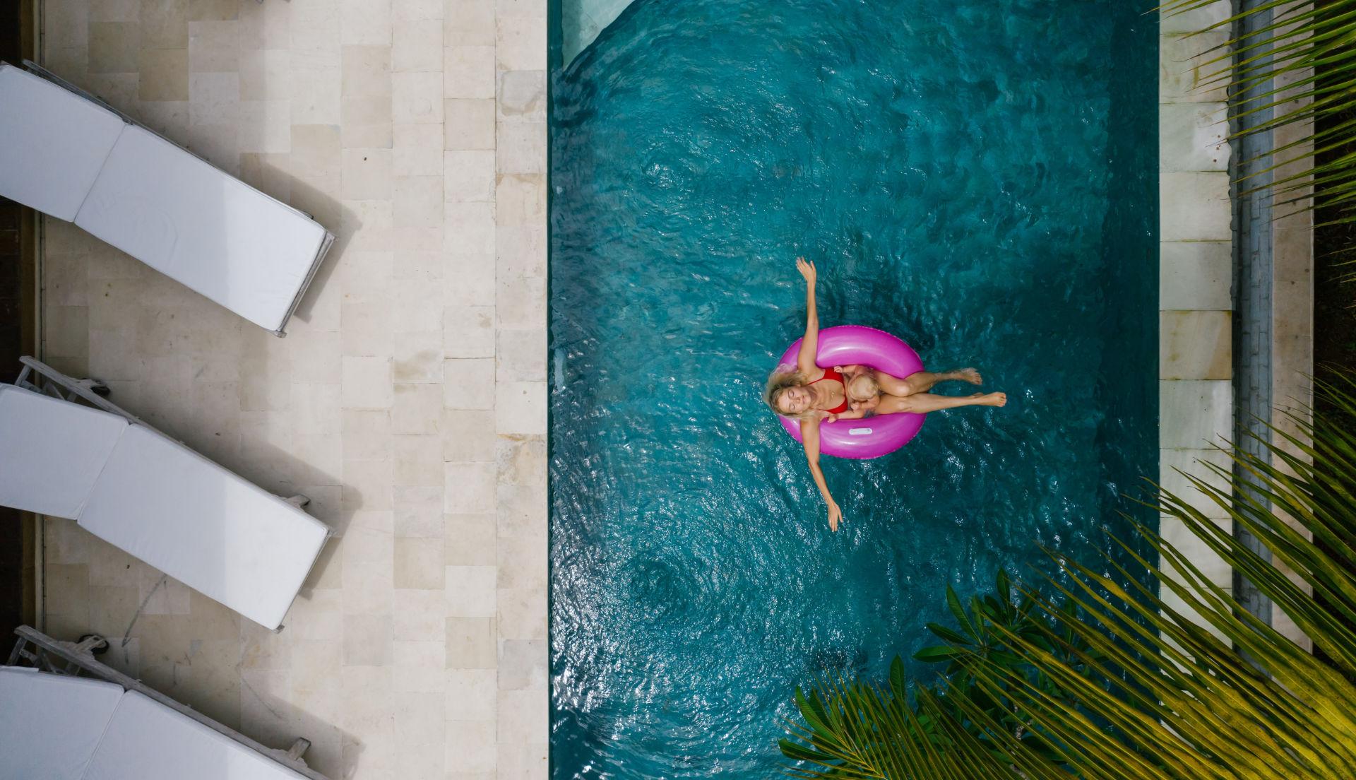 žena na ružovom nafukovacom kolese v bazéne